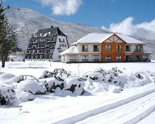 An exterior view of the Catedral Ski Village resort covered in snow.