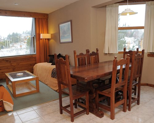 A well furnished living and wooden dining area with an outside view.