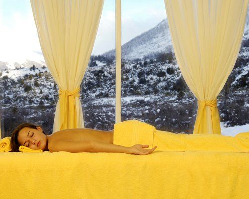 A woman relaxing in a spa room with an outside view.