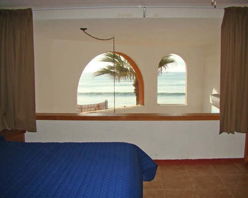 A furnished bedroom with a beach view.