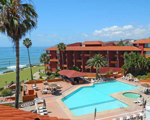 An outdoor swimming pool alongside the resort and the beach.