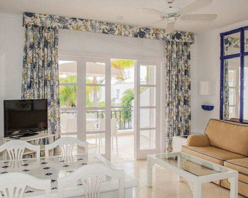 A well furnished living room with television and balcony.