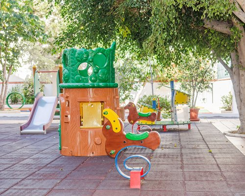 An outdoor kids playscape surrounded by trees.