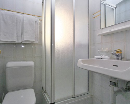 A bathroom with standing shower and single sink vanity.