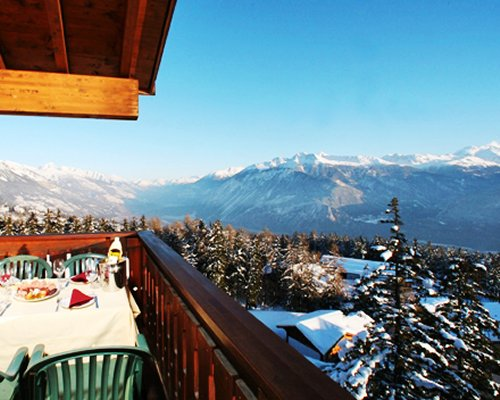 Restaurant at a balcony with view of wooded area and mountains during winter.