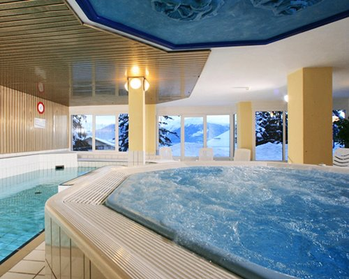 An indoor swimming pool with hot tub and an outside view.