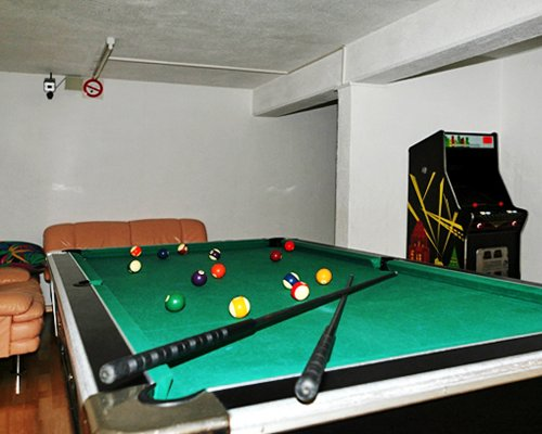 Indoor recreation area with arcade games and pool table.