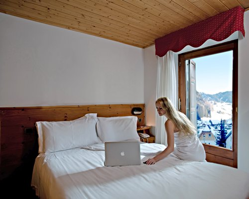 A woman using a laptop on a well furnished bedroom.