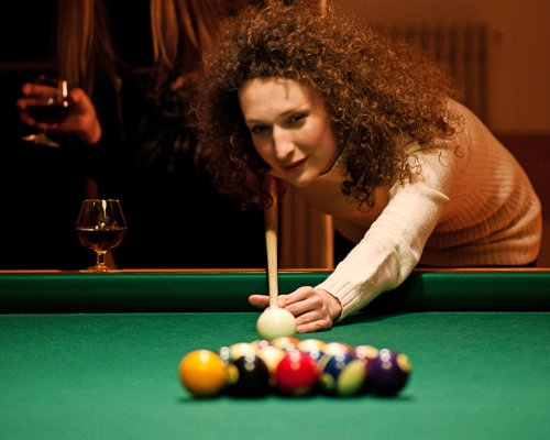 A woman playing pool ball.