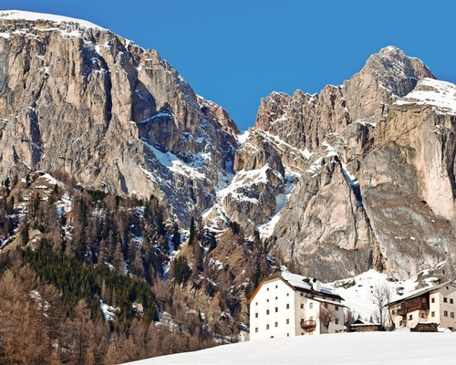 Exterior view of units at Domina Home Miramonti surrounded by mountains during winter.