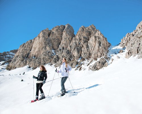 Two people skiing in the snow alongside rocks.