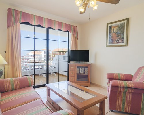 A well furnished living room with a television and a balcony.
