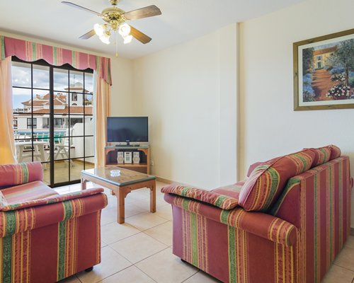 A well furnished living room with television and outside view.