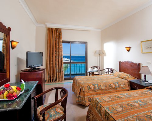 A well furnished bedroom with two twin beds television balcony and sea view.