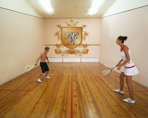 People playing racquetball at indoor recreation room.