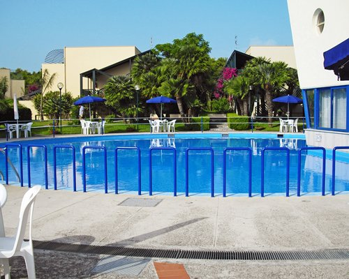 An outdoor swimming pool alongside resort units and landscaping.