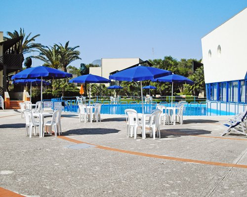Outdoor restaurant with sunshades alongside swimming pool.