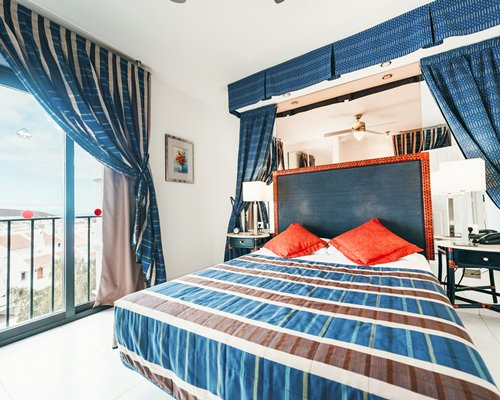 A well furnished bedroom with a balcony.