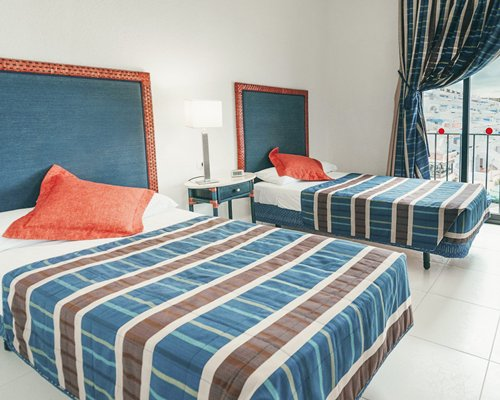 A well furnished bedroom with two beds and a balcony.