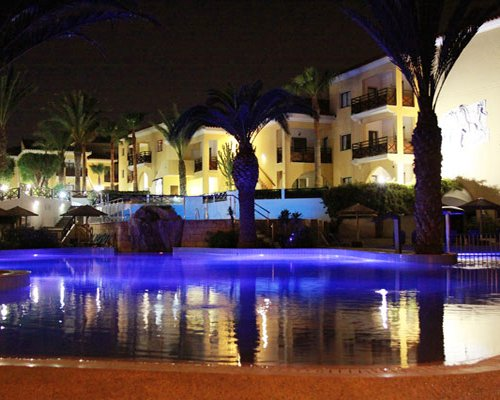 An outdoor swimming pool alongside multi story resort units at night.