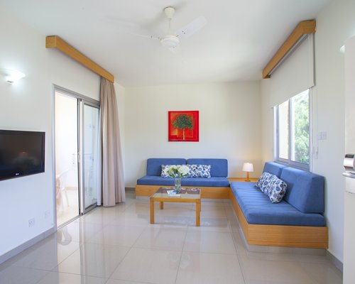 A well furnished living room with open plan kitchen breakfast bar television and outside view.