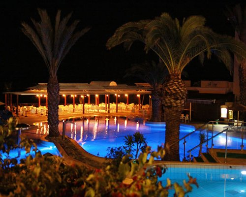 An outdoor swimming pool alongside a restaurant at night.
