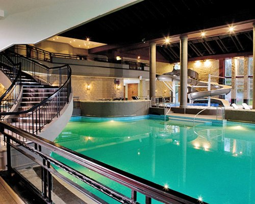 Indoor swimming pool with stairway and water slide.