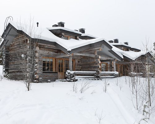 An exterior view of Holiday Club Rukaloma covered in snow.