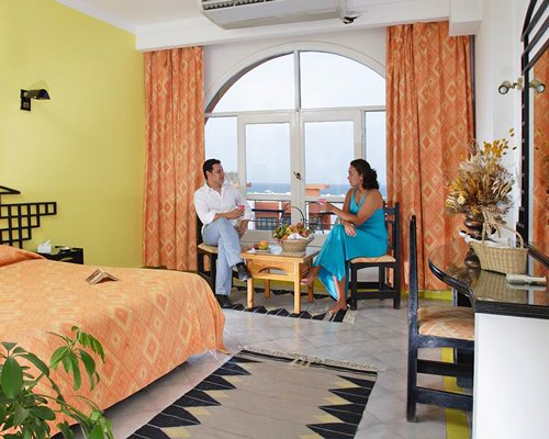 A couple at well furnished bedroom with balcony and sea view.