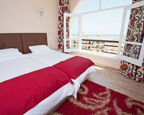 A well furnished bedroom with twin beds and ocean view.