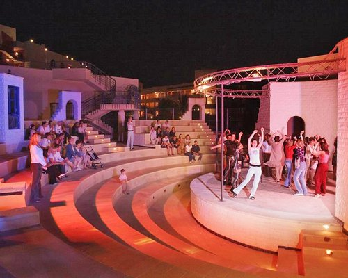 View of people dancing on a stage at an outdoor entertainment area.
