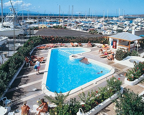 An outdoor swimming pool with chaise lounge chairs and marina.