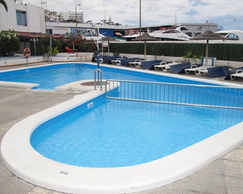 An outdoor swimming pool with hot tub and chaise lounge chairs alongside the resort units.