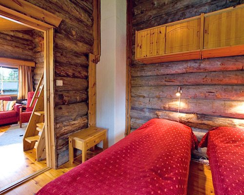 A wooden themed bedroom with two beds.