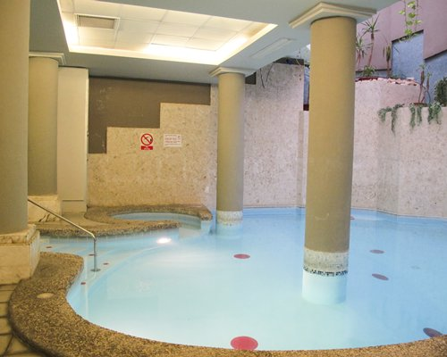 Indoor swimming pool with a hot tub.