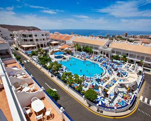 An aerial view of outdoor swimming pool with chaise lounge chairs sunshades and ocean view.