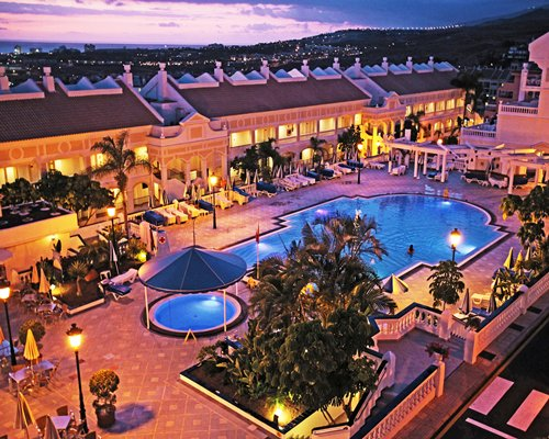 An aerial view of the resort with swimming pool at dusk.