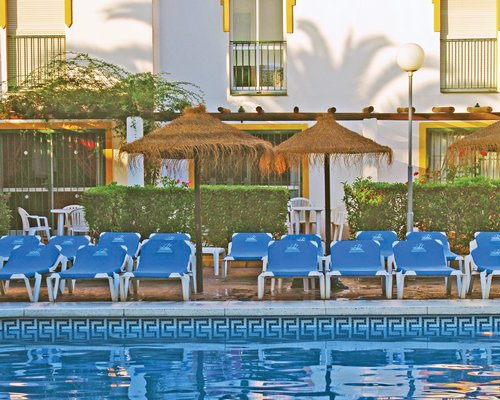 An outdoor swimming pool with patio furniture and thatched sunshades alongside resort units.