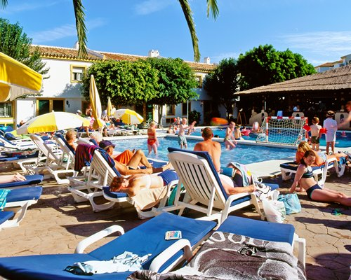 A group of people enjoying swimming in an outdoor pool alongside chaise lounge chairs.