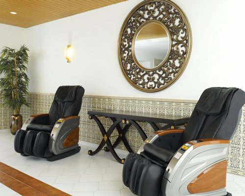 A well furnished indoor room with two massage chairs.