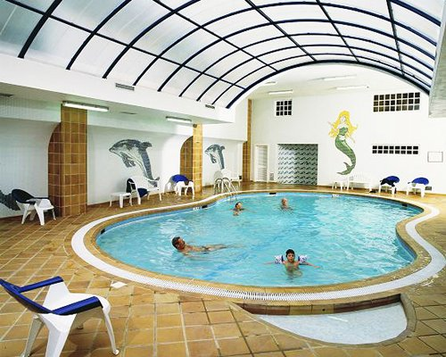 A large indoor swimming pool alongside patio furniture.