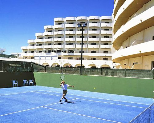 A person playing in a tennis court alongside resort units.