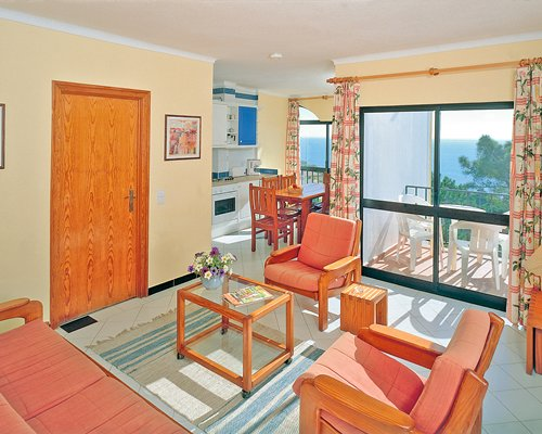 A well furnished living room with kitchen and balcony.