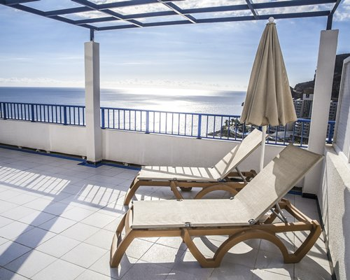 A balcony view of the ocean with chaise lounge chairs.