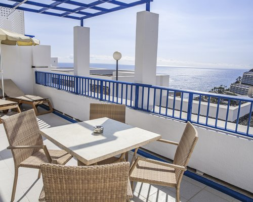An outdoor dining area with chaise lounge chairs and sunshades in the balcony.