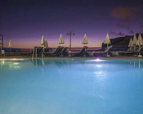 An outdoor swimming pool with chaise lounge chairs alongside the ocean at dusk.