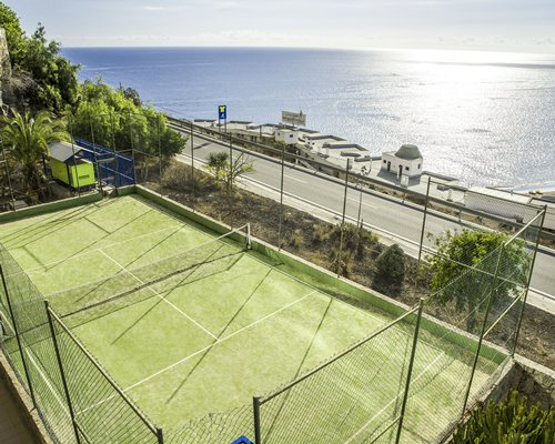 An outdoor tennis court alongside the ocean.