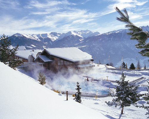 An exterior view of the resort covered in snow with large hot tub.