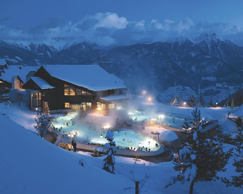 An outdoor swimming pool alongside the resort surrounded by a snowy mountain at dusk.