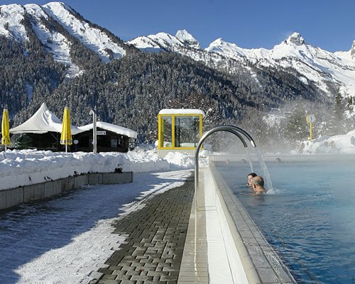 Outdoor swimming pool alongside a pathway surrounded by mountains during winter.